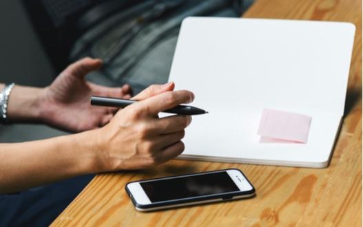 En hand håller i en penna ved ett anteckningsblock och en telefon